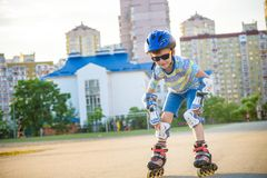 Little boy riding on rollers in the summer in the Park. Happy ch royalty free stock image