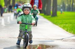 Little boy riding a runbike. On a rainy day Stock Photography