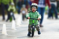 Little boy riding a runbike. On a rainy day Stock Images