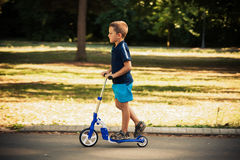 Little boy riding scooter in park Stock Image