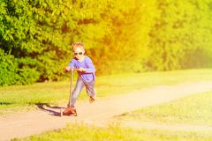 Little boy riding scooter in summer park Stock Photography