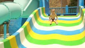 Little boy is riding a slide in water park, slowmo stock video footage