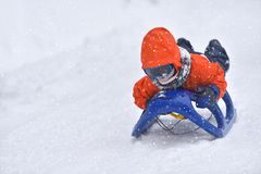 Little boy riding on snow slides in winter time royalty free stock photography
