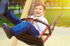 Little boy riding on a swing Stock Photo