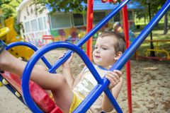 Little boy riding on a swing in a park stock image