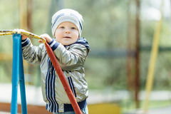 Little boy riding a swing in park playground. Spring Stock Photo