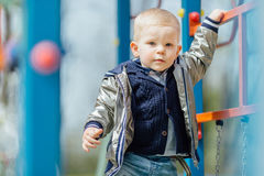 Little boy riding a swing in park playground. Spring Stock Photography