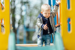 Little boy riding a swing in park playground. Spring Royalty Free Stock Images