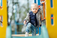Little boy riding a swing in park playground. Spring Royalty Free Stock Photos