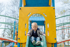 Little boy riding a swing in park playground. Spring Stock Images