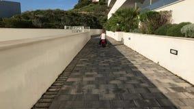 Little boy riding toy motor bike stock footage