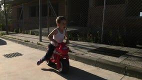 Little boy riding toy motor bike stock video footage