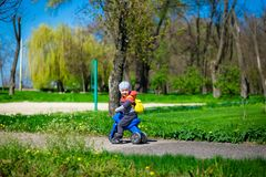 Little boy riding toy motorbike in green sunny park. Active childhood Stock Photos