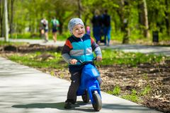 Little boy riding toy motorbike in green sunny park. Active childhood Stock Photography