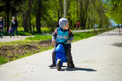 Little boy riding toy motorbike in green sunny park. Active childhood Stock Image