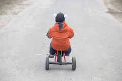 The little boy is riding a tricycle royalty free stock photo