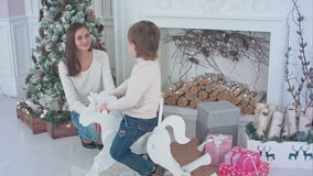 Little boy riding wooden rocking horse while his mom sitting next to Christmas fireplace stock video footage