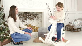 Little boy riding wooden rocking horse and talking to his mother sitting near the Christmas tree stock footage