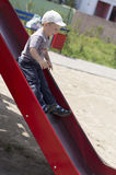 Little boy rids on the slide Stock Photos