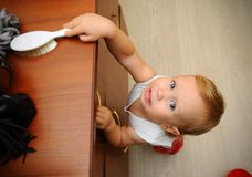 Little boy risking accident with falling furniture. Photo warns parents about the hidden dangers that pose a risk to children in their homes royalty free stock photo