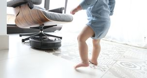 Little boy and robot vacuum cleaner on the floor stock footage