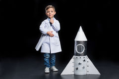 Little boy with rocket. Little boy in white coat with finger on chin holding blueprints near toy rocket Royalty Free Stock Photos