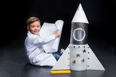 Little boy with rocket. Little boy in white coat holding blueprint while sitting near toy rocket and smiling at camera Royalty Free Stock Photography