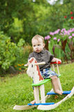 Little boy on the rocking horse. Outdoors Royalty Free Stock Photos
