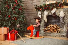 Little boy on rocking horse in Christmas interior stock photo