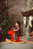 Little boy on rocking moose in Christmas interior stock photography
