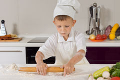 Little boy rolling out dough in the kitchen Stock Images