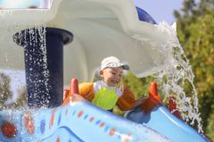 A little boy rolls down a water slide. Children`s joy in the water park. Summer vacation for children in the water park stock photos