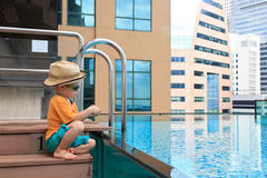 Little boy playing in roof top pool Royalty Free Stock Photos