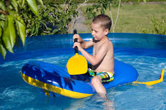 Little boy is rowing in the pool Stock Images