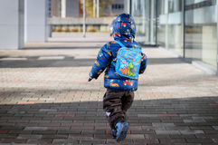 Little boy with rucksack is  running on a street Royalty Free Stock Image