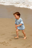 Little boy runing from ocean waves. Little boy running on sand from ocean waves Royalty Free Stock Image
