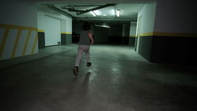 Little boy runing in underground garage, Child around spacious dimly lit parking lot for cars. Little boy runing in underground garage. Child around spacious stock footage