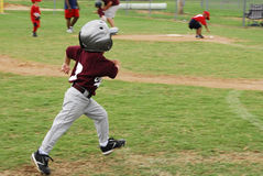 Little Boy Running. Around the field to score at a T-ball game Stock Photo