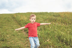 Little boy running across the field on the lawn on a summer day Royalty Free Stock Photography