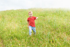 Little boy running across the field on the lawn on a summer day Royalty Free Stock Photos