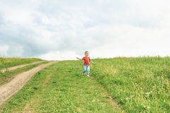Little boy running across the field on the lawn on a summer day Stock Images