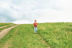Little boy running across the field on the lawn on a summer day Stock Photo