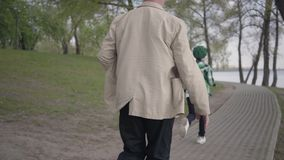 Little boy running away from his grandfather in the park. The old man chasing the boy, but he is tired and stopped to