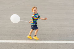 Little boy running with a balloon Royalty Free Stock Images
