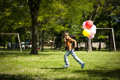 Little boy running with balloons. Little boy running while holding balloons Royalty Free Stock Images