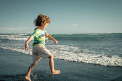 Little boy running on the beach Stock Images
