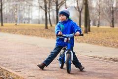 Little boy on running bike in autumn Stock Images