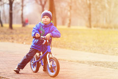 Little boy on running bike in autumn Royalty Free Stock Images