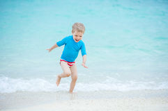Little boy running in breaking waves on the beach Stock Images
