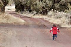 Little Boy Running Down Dirt Road Stock Photo